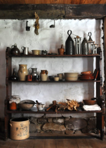 A collection of period and reproduction dishes and other kitchen tools as displayed in the Wyckoff farmhouse's 17th-century kitchen
