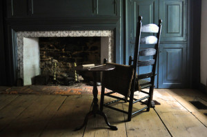 """A high-backed wooden chair, side table, bone pipe, and formal hearth in the museum's 18th-century """"formal parlor"""""""