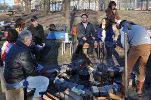 A group of adult visitors to the Wyckoff farmhouse gathers around the outdoor hearth
