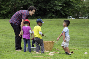 Three young children explore colonial games and toys during a summer family day at the Wyckoff House Museum