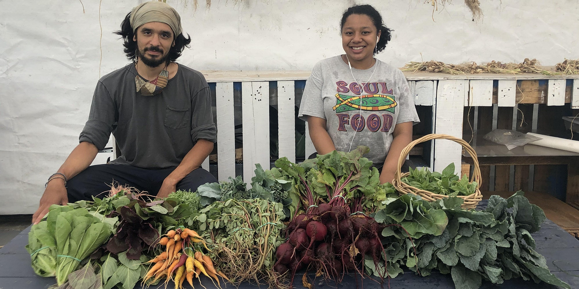 Farmers Zach & Anissa in front of a harvest of vegetables from the Wyckoff Farm.